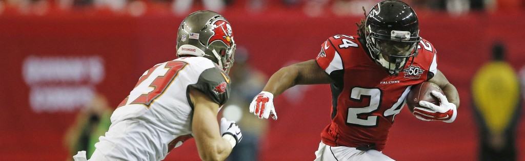 Atlanta Falcons running back Devonta Freeman (24) runs as Tampa Bay Buccaneers strong safety Chris Conte (23) defends during the first of an NFL football game, Sunday, Nov. 1, 2015, in Atlanta. (AP Photo/John Bazemore)