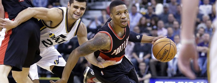 Portland Trail Blazers guard Damian Lillard (0) drives around Utah Jazz guard Raul Neto, left, in the first quarter during an NBA basketball game Wednesday, Nov. 4, 2015, in Salt Lake City. (AP Photo/Rick Bowmer)
