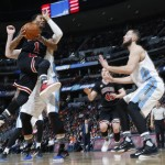 Chicago Bulls guard Derrick Rose, front left, drives the lane and is fouled by Denver Nuggets center Jusuf Nurkic as Nuggets center Joffrey Lauvergne, right, defends during the second half of an NBA basketball game Friday, Feb. 5, 2016, in Denver. The Nuggets won 115-110. (AP Photo/David Zalubowski)