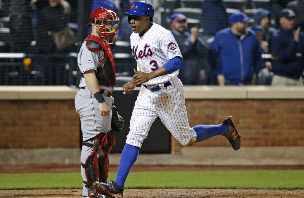 New York Mets' Curtis Granderson (3) scores the go-ahead run on David Wright's seventh-inning single in the Mets' 4-3 victory over the Cincinnati Reds as Reds catcher Tucker Barnhart, left, watches, in a baseball game Tuesday, April 26, 2016, in New York. (AP Photo/Kathy Willens)