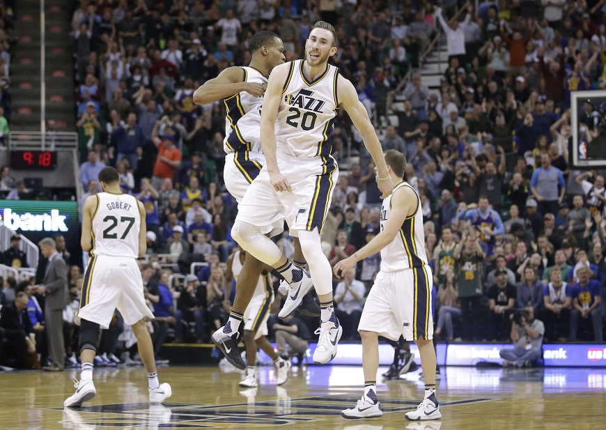 Utah Jazz's Rodney Hood, center left, celebrates with Gordon Hayward (20) during the second half of an NBA basketball game against the Golden State Warriors Wednesday, March 30, 2016, in Salt Lake City. The Warriors won 103-96 in overtime. (AP Photo/Rick Bowmer)